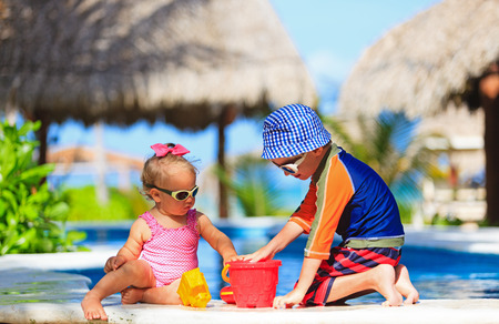swimming pool: little boy and toddler girl playing in swimming pool at beach