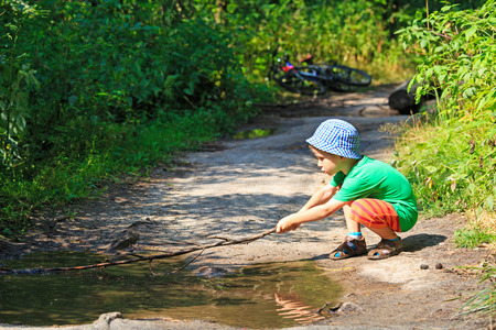 wooden stick: little boy playing with a stick in water puddle on summer