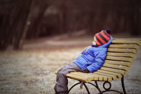lonely child sitting on bench in park, winter depression