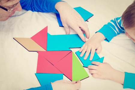 early learning: hands of teacher and child playing with geometric shapes, early learning