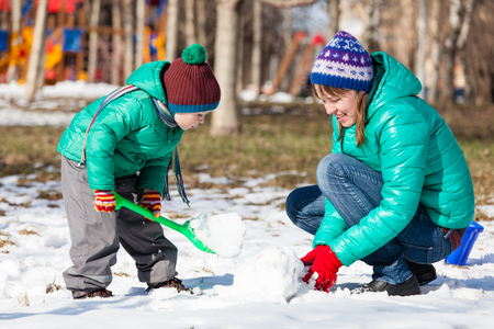 snowman: mother and son building snowman in winter park Stock Photo