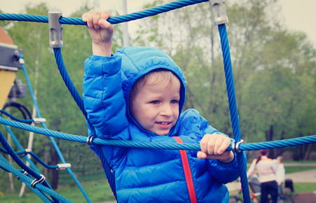 ni�o escalando: little boy climbing rope on the playground outdoors Foto de archivo