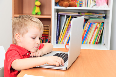 early learning: little boy working on laptop at home, early learning