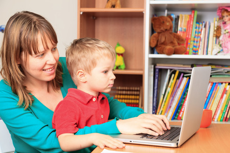 working mother: mother working on laptop from home with little son Stock Photo