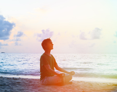 meditation man: Silhouette of young man meditating at sunset beach Stock Photo