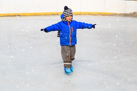 snow ice: cute little boy learning to skate in winter snow