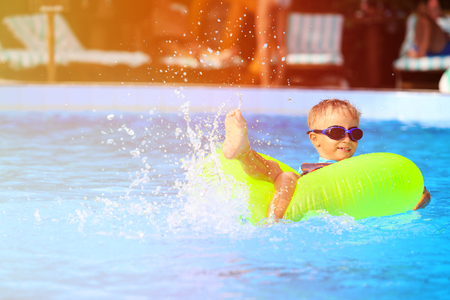 cute little boy in life ring having fun in the swimming pool
