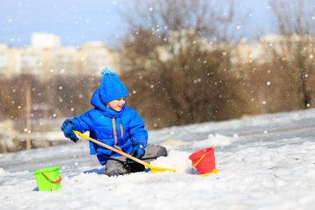 digging: little boy digging snow in winter, kids winter activities