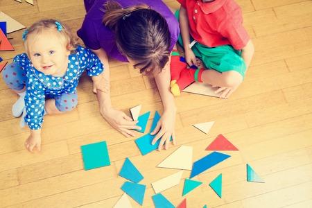 kinder: profesor y niños jugando con formas geométricas, el aprendizaje temprano