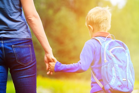 Mother holding hand of little son with backpack outdoors, back to school Stock Photo