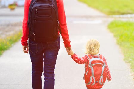 niños en la escuela: Madre de la mano de la pequeña hija con la mochila de ir a la escuela o guardería