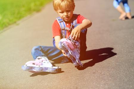 niño en patines: niño pequeño lindo poner en patines de ruedas al aire libre