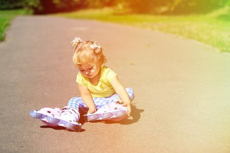 put on: cute little girl put on roller skates outdoors
