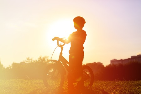 bicycle race: little boy riding bike at sunset, active kids sport