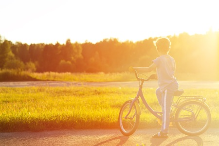 active lifestyle: little boy riding bike at sunset, kids sport and  active lifestyle Stock Photo
