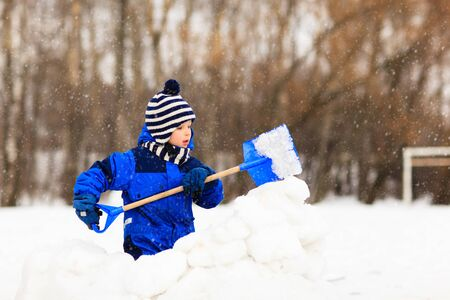 dig: little boy dig and play in winter snow, kids winter activities