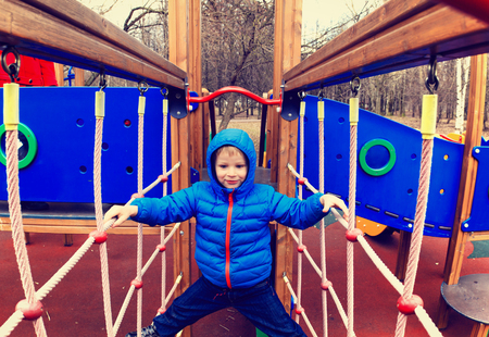 on playground: little boy climbing on the web in playground, kids sport