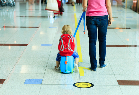 mother and little daugther on suitcase walk in the airport, family travel