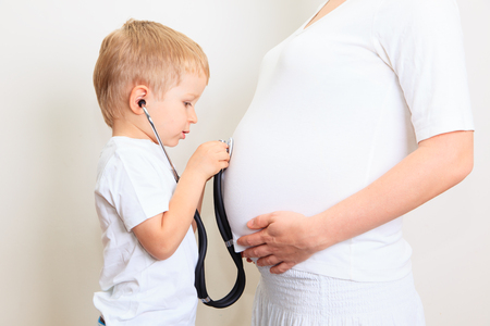 sibling: Little boy excited about her coming sibling - listening to mothers tummy