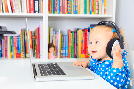 early learning: little girl with headphones and laptop, early learning