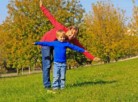 outoors: mother and son flying in autumn park, family fun