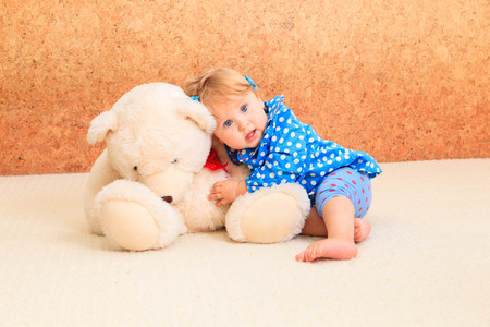 indoors: little girl playing with teddy bear indoors Stock Photo
