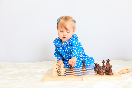 early learning: cute little girl playing chess indoors, early learning