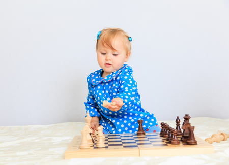 indoors: cute little girl playing chess indoors, early learning