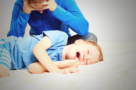 disobedient child: crying child, tired father, difficult parenting concept Stock Photo