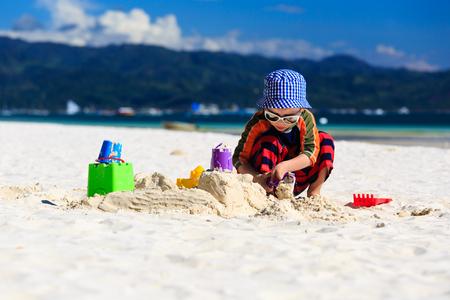sandcastle: child building sandcastle on tropical sand beach Stock Photo