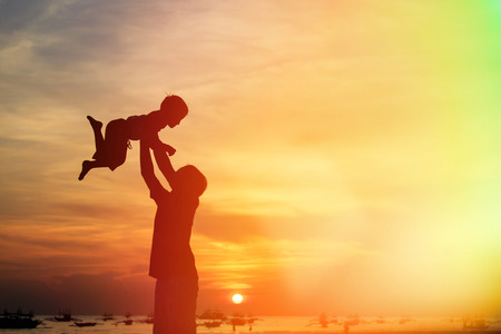 fun in the sun: father and son silhouettes play at sunset beach