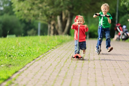 little boy and toddler girl riding scooters in summer park, kids sport