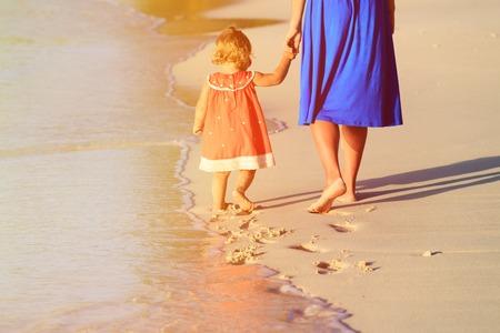 母と小さな娘が砂、家族のビーチ旅行の足跡を残すビーチの上を歩く 写真素材