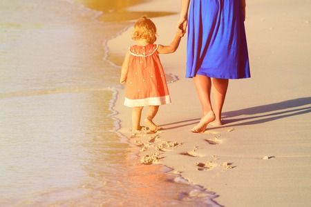 footprints in the sand: mother and little daughter walking on beach leaving footprint in the sand, family beach travel