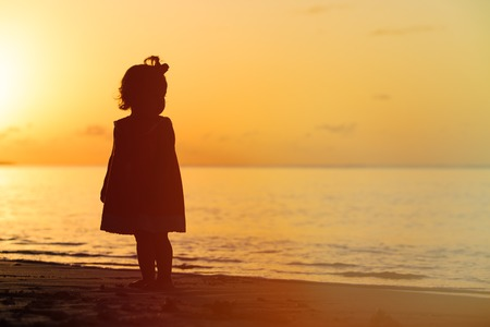 kids playing beach: silhouette of little girl walking at sunset beach
