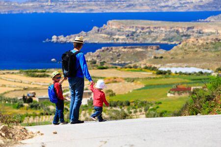 mochila viaje: father with two kids walking on scenic road, family travel Foto de archivo
