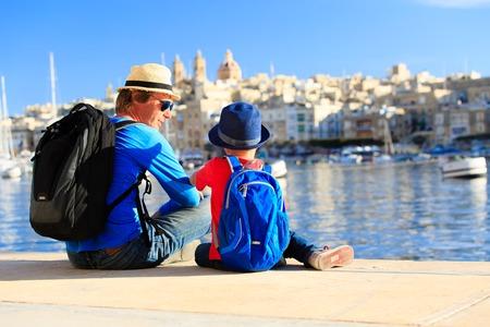 niño con mochila: padre e hijo mirando ciudad de La Valeta, Malta, los viajes familiares Foto de archivo
