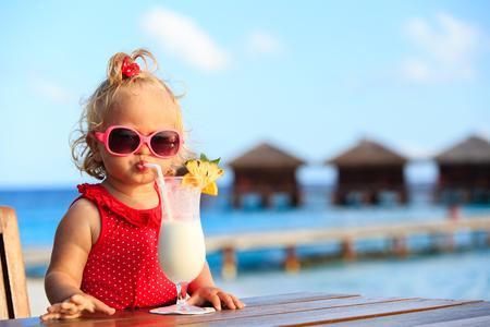 열 대 해변 휴양지에 귀여운 소녀 마시는 칵테일