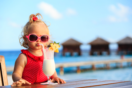 drink at the beach: cute little girl drinking cocktail on tropical beach resort