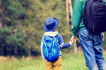 young parents: father holding hand of little son with backpack outdoors, back to school or daycare Stock Photo