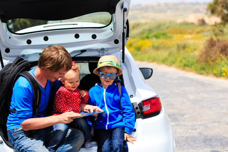 active lifestyle: father with two kids looking at map while travel by car