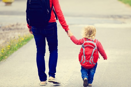 学校や保育園に行くのバックパックと小さな娘の手を握って母