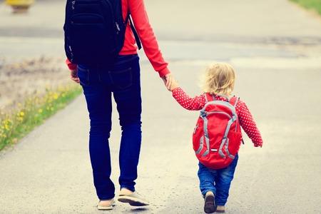 Moeder die de hand van dochtertje met rugzak gaat naar school of kinderopvang Stockfoto