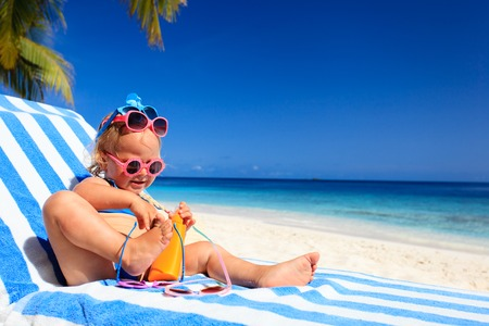little girl swimsuit: happy cute little girl trying on sunglasses at the beach