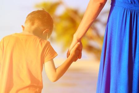 母と息子の夏のビーチを手をつないで