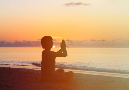 and the horizontal man: Silhouette of young man doing yoga at sunset beach