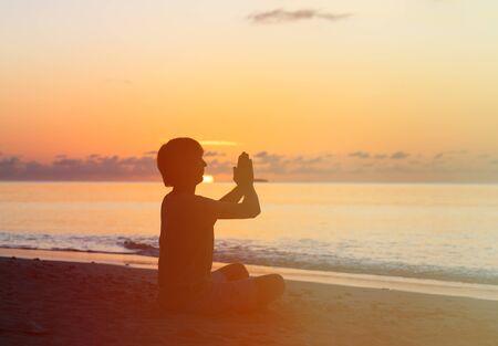 hombre solo: Silueta del hombre joven que hace yoga en la playa de la puesta del sol