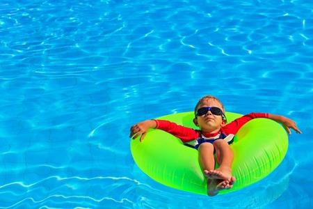 little boy in life ring having fun on summer beach 写真素材