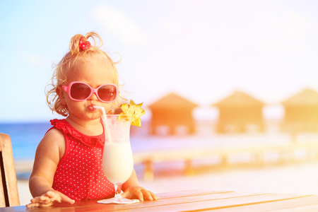cute little girl drinking cocktail on tropical beach resort