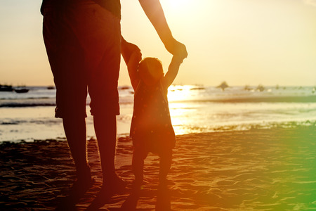apoyo familiar: father and little daughter learning to walk on sunset beach